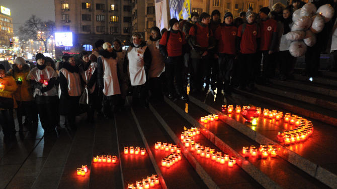 Ukrainian people make a red ribbon sign with candles ahead of the World AIDS Day, in Kiev, Ukraine, Thursday, Nov. 29, 2012. (AP Photo/Sergei Chuzavkov)