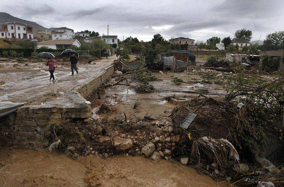 Residents walk on a muddy street after heavy rain caused flash floods in the town of Villanueva del Rosario, Malaga, southern Spain, Friday, Sept. 28, 2012. Homes were destroyed and at least one woman was killed. Rescue workers are searching to determine if there are more victims.(AP Photo/Sergio Torres)