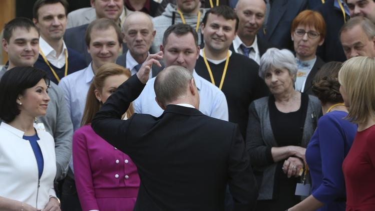 Russian President Putin talks to participants after a live broadcast nationwide phone-in in Moscow