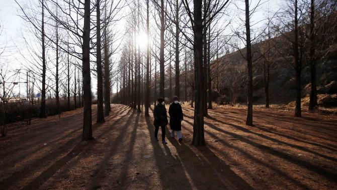Women take a walk on a cold winter day at a park in Seoul