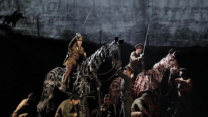 """FILE - In this theater publicity image released by Lincoln Center Theater, a scene is shown from the production of """"War Horse,"""" performing at the Lincoln Center Theater in New York.  Best-selling author Michael Morpurgo, who wrote the book the Tony Award-winning play is based on, was part of more than a dozen actors watching the auctioning-off of the horse Joey at the top of the show. The author, who made a similar appearance in the London production of """"War Horse"""" and is an extra in Steven Spielberg's movie version, didn't speak any dialogue and didn't appear again until the curtain call a few hours later. (AP Photo/Lincoln Center Theater, Paul Kolnik)"""