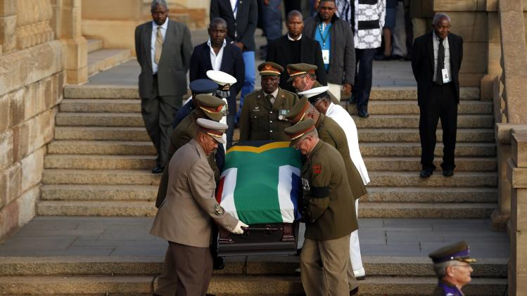 Mandla Mandela, the eldest grandson of former South African President Nelson Mandela, watches as Mandela's flag-draped coffin is carried down steps of the Union Buildings in Pretoria