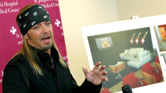 Poison frontman Bret Michaels talks about the designs for a music room he will be funding and decorating, with renderings of the space in the background, at St. Joseph's Hospital and Medical Center Barrow Neurological wing Thursday, Oct. 27, 2011, in Phoenix.  Michaels is a former patient at the Barrow Neurological center, after suffering a type of life-threatening stroke in 2010. (AP Photo/Ross D. Franklin)