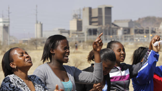 Women from a group of churchgoers  wail at the site, Sunday Aug. 19, 2012 at the Lonmin platinum mine, background, near Rustenburg, South Africa, during a memorial service for 34 dead striking miners who were shot and killed by police last Thursday.   Miners must return to work Monday or face being fired from the  mine where rivalry between unions has exploded into violence.  (AP Photo/Denis Farrell)