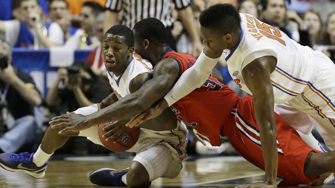 Florida guard Kenny Boynton, left, Mississippi forward Murphy Holloway (31) and Florida forward Will Yeguete (15) vie for a loose ball during the first half of an NCAA college basketball game in the final round of the Southeastern Conference tournament, Sunday, March 17, 2013, in Nashville, Tenn. (AP Photo/Dave Martin)