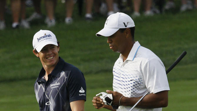 Rory McIlroy of Northern Ireland, left,  smiles at Tiger Woods on the second fairway during the second round of the BMW Championship PGA golf tournament at Crooked Stick Golf Club in Carmel, Ind., Friday, Sept. 7, 2012. (AP Photo/Charles Rex Arbogast)