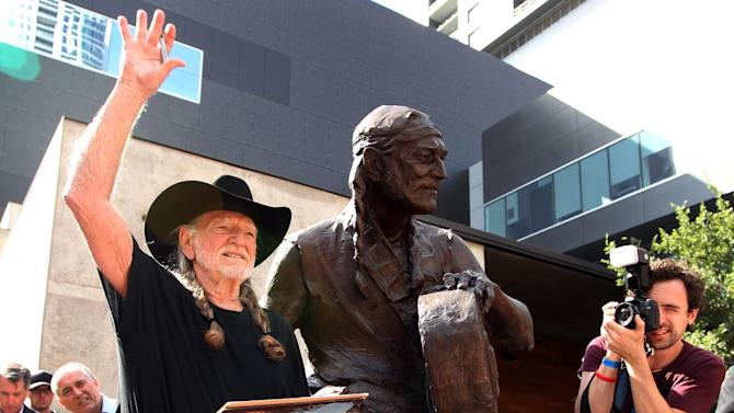 Country singer Willie Nelson waves during the unveiling of an eight-foot statue of himself, Friday, April 20, 2012 in Austin, Texas. The privately-funded monument near the new Moody Theater shows Nelson in a relaxed, standing pose and holding his guitar to the side, as if in conversation.  (AP Photo/Austin American-Statesman, Jay Janner)  MAGS OUT; NO SALES; INTERNET AND TV MUST CREDIT PHOTOGRAPHER AND STATESMAN.COM