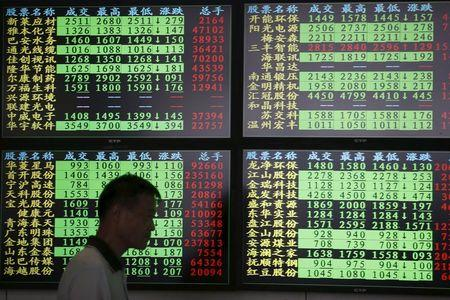 An investor walks past as information displayed on an electronic screen at a brokerage house in Shanghai