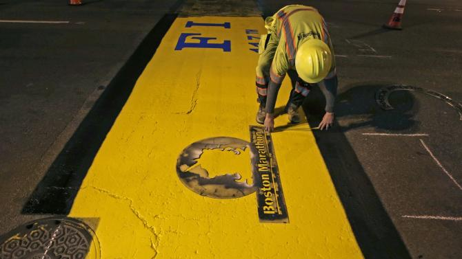 In this Monday, April 29, 2013, photo, Will Belezos measures the placement of the Boston Marathon logo while repainting the finish line two weeks after the race that was disrupted by two tragic explosions in Boston. Maintenance on the finish line, which typically involves the race-day sticker being pulled up after the event and the paint version touched up as the more permanent parker, was delayed until the crime scene was cleared. (AP Photo/Charles Krupa)