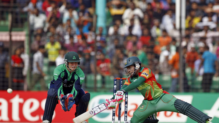 Bangladesh's Mushfiqur Rahim, right, plays a shot in front of Ireland's wicketkeeper Gary Wilson during a warm up cricket match between them ahead of the ICC World Twenty20 Cricket tournament in Fatullah, near Dhaka, Bangladesh, Friday, March 14, 2014. (AP Photo/A.M. Ahad)