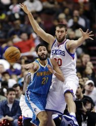 New Orleans Hornets&#39; Greivis Vasquez (21) passes the ball as Philadelphia 76ers&#39; Spencer Hawes defends during the first half of an NBA basketball game, Tuesday, Jan. 15, 2013, in Philadelphia. (AP Photo/Matt Slocum)