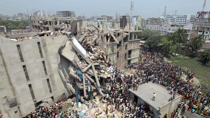 People and rescuers gather after an eight-story building housing several garment factories collapsed in Savar, near Dhaka, Bangladesh, Wednesday, April 24, 2013. Dozens were killed and many more are feared trapped in the rubble. (AP Photo/ A.M. Ahad)