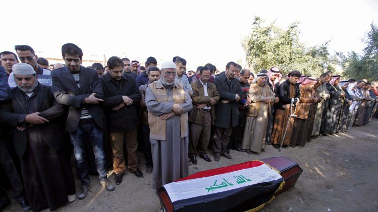 Mourners pray next to the coffin of Joumaili during his funeral in Falluja