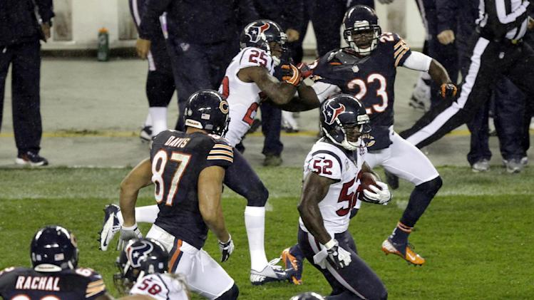 Houston Texans linebacker Tim Dobbins (52) runs after recovering a fumble by Chicago Bears tight end Kellen Davis (87) during the first half of an NFL football game, Sunday, Nov. 11, 2012, in Chicago. Davis made the tackle on Dobbins. (AP Photo/Kiichiro Sato)
