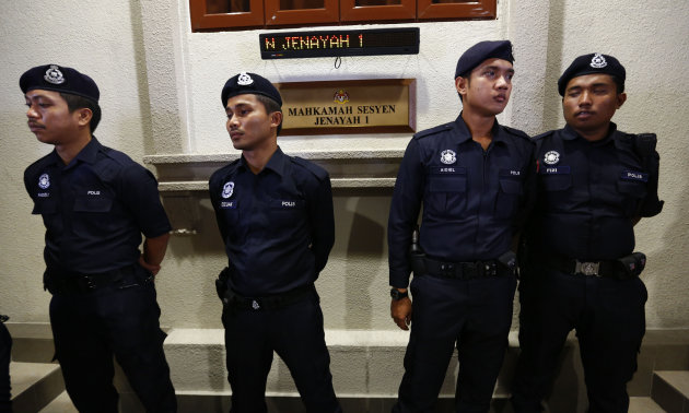 Police stand guard outside a court room in Kuala Lumpur, Malaysia, Thursday, May 23, 2013. Prosecutors filed a sedition charge Thursday against a student activist who urged Malaysians to engage in str