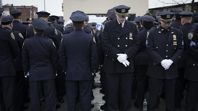 Some police officers turn their backs in sign of disrespect as Mayor Bill de Blasio speaks during the funeral of New York Police Department Officer Wenjian Liu at Aievoli Funeral Home, Sunday, Jan. 4, 2015, in the Brooklyn borough of New York. Liu and his partner, officer Rafael Ramos, were killed Dec. 20 as they sat in their patrol car on a Brooklyn street. The shooter, Ismaaiyl Brinsley, later killed himself. (AP Photo/John Minchillo)