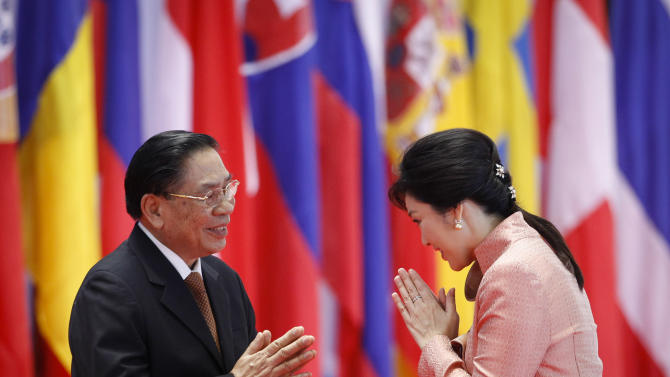 Lao President Choummaly Sayasone, left, greets Thai Prime Minister Yingluck Shinawatra as she arrives for the opening ceremony for the ASEM Summit in Vientiane, Laos, Monday, Nov. 5, 2012. (AP Photo/Vincent Thian)