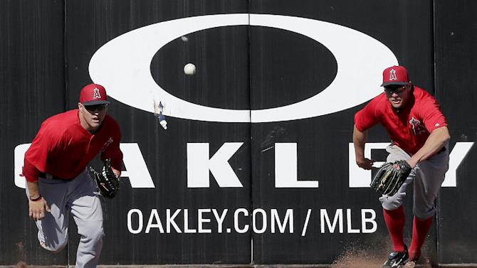 Los Angeles Angels left fielder Mike Trout, left, and center fielder Peter Bourjos chase after a triple hit by Seattle Mariners' Dustin Ackley during an exhibition spring training baseball game, Monday, Feb. 25, 2013, in Peoria, Ariz. (AP Photo/Charlie Riedel)