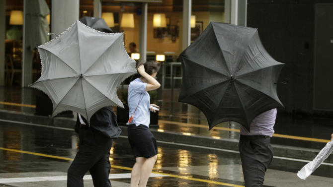 People struggle to hold onto their umbrellas as Typhoon Bolaven brings heavy downpours and winds to South Korea, at Gimpo Airport in Seoul, South Korea, Tuesday, Aug. 28, 2012. (AP Photo/Ahn Young-joon)