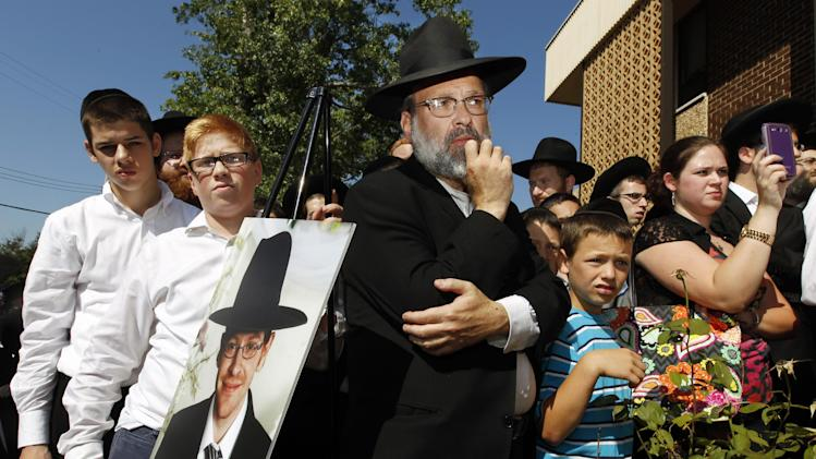 A photograph of Aaron Sofer, 23, is nearby as people listen during a news conference Tuesday, Aug. 26, 2014, in Lakewood, N.J. Israeli police said Tuesday they are searching for the young New Jersey religious student who went missing during a hike in a forest outside Jerusalem last week. Sofer of Lakewood, New Jersey, has been missing since Friday when he went on a hike with a friend in the Jerusalem Forest, said police spokesman Micky Rosenfeld. Rosenfeld said that police have launched an extensive search for Sofer, who is an ultra-Orthodox student at a yeshiva — a Jewish religious school. Sofer's parents have flown to Israel. (AP Photo/Mel Evans)