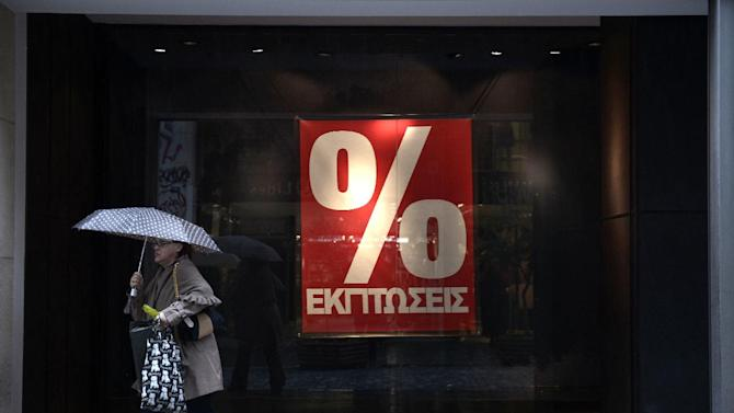 A woman walks past a shop in central Athens on the first day of the winter sales on January 12, 2015