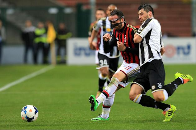 AC Milan's Giampaolo Pazzini, left, and Udinese's Igor Bubnjic fight for the ball during the Serie A soccer match between Udinese and AC Milan at the Friuli Stadium in Udine, Italy, Saturday,