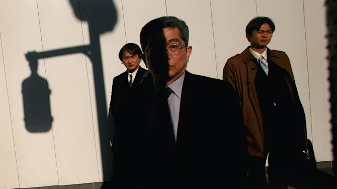 FILE - In this Jan. 30, 2007 file photo, Japanese businessmen wait at a street crossing in Tokyo. Japanese manufacturers remain gloomy over high oil prices, the strong yen and weaker growth in Asia, according to a quarterly central bank survey released Monday, April 2, 2012 that defied expectations that business confidence was improving in the world's third-largest economy. (AP Photo/David Guttenfelder, File)
