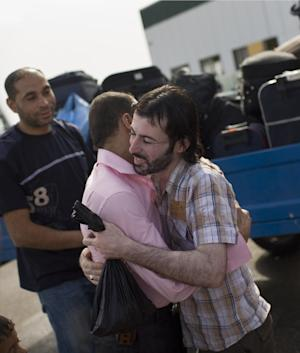 Palestinian Yasser Srsaui, right, embraces a family member before crossing into Egypt through the Rafah border crossing, southern Gaza Strip, Saturday, May 28, 2011. After four years, Egypt on Saturday permanently opened the Gaza Strip's main gateway to the outside world, bringing long-awaited relief to the territory's Palestinian population and a significant achievement for the area's ruling Hamas militant group. (AP Photo/Bernat Armangue)
