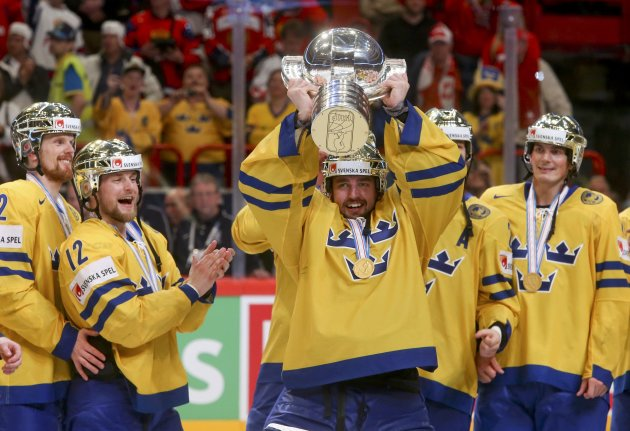 Sweden's goalie Enroth lifts up the trophy as he celebrates with team mates their victory over Switzerland in their 2013 IIHF Ice Hockey World Championship final match at the Globe Arena in Stockholm