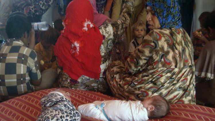 Iraqi Shiite Turkmen families rest at a temporary shelter after arriving in Kanaan