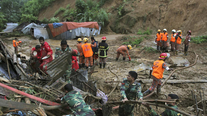 Bangladeshi rescuers search for survivors and bodies following landslides on the outskirts of Chittagong, Bangladesh, Wednesday, June 27, 2012.  Rescuers said the slides caused by heavy monsoon rains have killed at least 30 people in southern Bangladesh. (AP Photo/Anrup Titu)