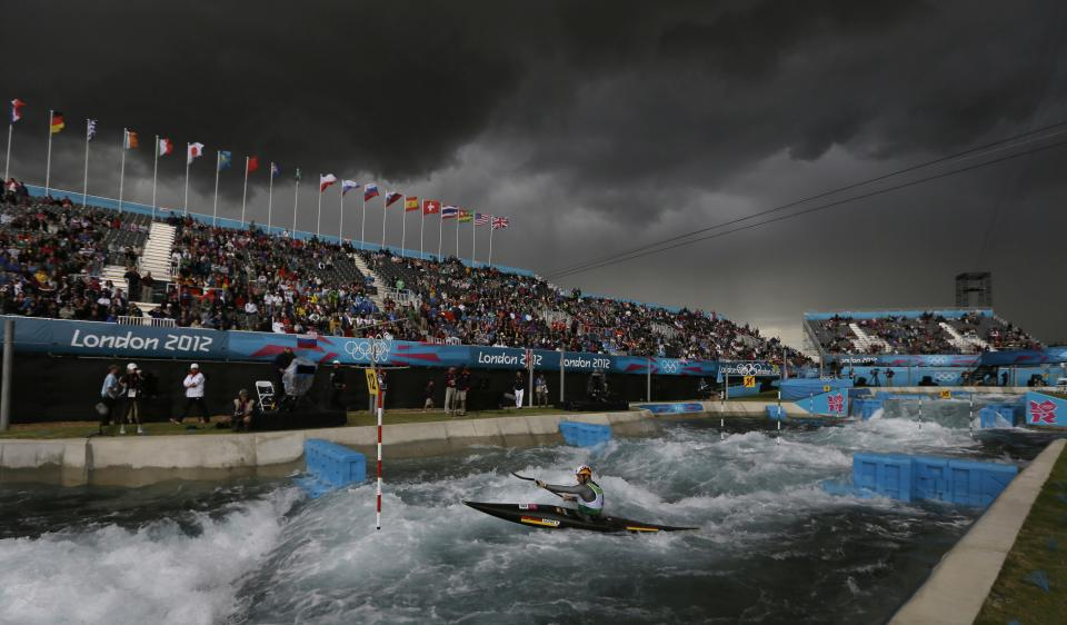 The sky turns black before a heavy rain shower as Germany's Hannes Aigner competes in the heats of the K-1 men's canoe slalom at Lee Valley Whitewater Center, at the 2012 Summer Olympics, Sunday, July 29, 2012, in London. (AP Photo/Kirsty Wigglesworth)