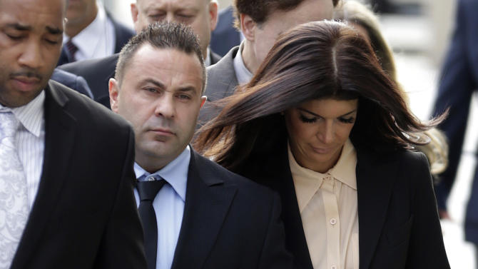 "FILE - In this Oct. 2, 2014, file photo, ""The Real Housewives of New Jersey"" stars Giuseppe ""Joe"" Giudice, center, and his wife, Teresa Giudice, right, of Montville Township, N.J., walk toward the Martin Luther King Jr. Courthouse before a court appearance, in Newark, N.J. Teresa Giudice is petitioning to serve most of her federal prison sentence in a halfway house. She was sentenced to 15 months in prison after she pleaded guilty to bankruptcy fraud and conspiracy. Her husband, Giuseppe ""Joe"" Giudice, was sentenced to 41 months. (AP Photo/Julio Cortez, File)"