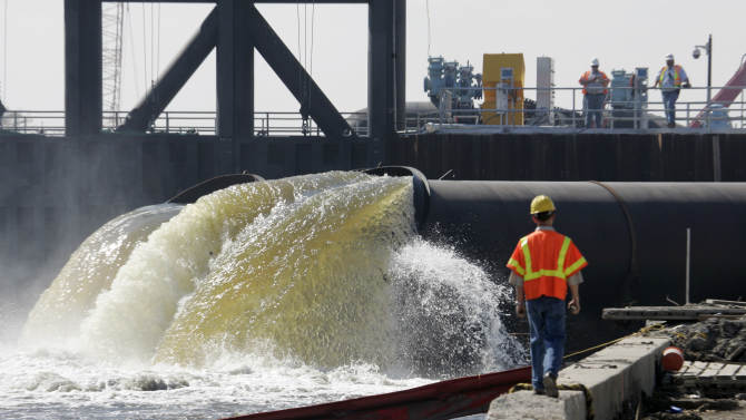 FILE - In this Saturday, March 10, 2007 file photo, Daren J. Eller watches as pumps put in place by the Army Corps of Engineers extract water from New Orleans' 17th Street Canal into Lake Pontchartrain in New Orleans. One of the levees along the canal failed during Hurricane Katrina, contributing heavily to the flooding of the city. The pumps and floodgate are designed to control the water level in the drainage canals during a storm event. (AP Photo/Bill Haber, File)