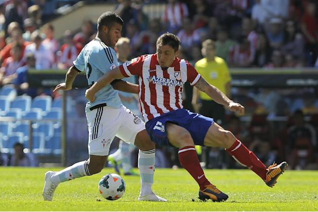 Atletico de Madrid's Cristian Rodriguez from Uruguay, right, in action with Celta de Vigo's Rafinha from Brazil, left, during a Spanish La Liga soccer match at the Vicente Calderon stadium in Madrid,