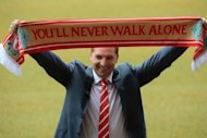 Newly appointed Liverpool manager Brendan Rodgers poses for photographers with a team scarf to announce his arrival at Anfield in Liverpool. Rodgers said he aimed to bring the glory days back to Liverpool after being appointed the new manager of the former kings of Engish football