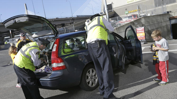 Fans watch as security officers check their vehicle on the way into TD Garden prior to a Boston Bruins hockey game against the Buffalo Sabres in Boston, Wednesday, April 17, 2013, in the aftermath of Monday's Boston Marathon bombings. (AP Photo/Elise Amendola)
