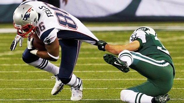 New England Patriots' Daniel Fells, left, is tackled by New York Jets' Eric Smith (Reuters)