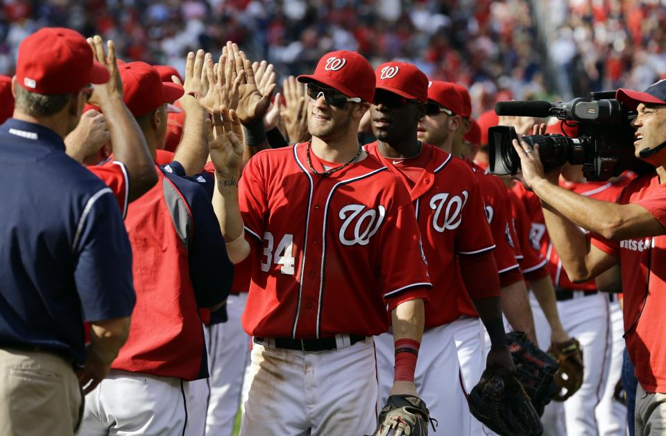 Washington Nationals center fielder Bryce Harper (34), and Washington Nationals right fielder Roger Bernadina (2), and others, celebrate after a baseball game against the Milwaukee Brewers at Nationals Park Saturday, Sept. 22, 2012, in Washington. The Nationals won 10-4. (AP Photo/Alex Brandon)