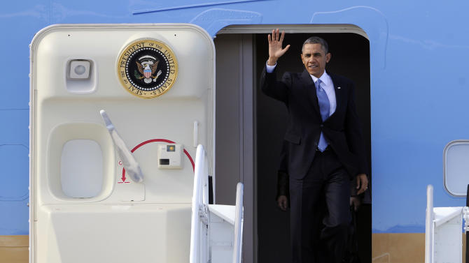 President Barack Obama waves as he exits Air Force One upon his arrival at McCarran International Airport Tuesday, Jan. 29, 2013 in Las Vegas. (AP Photo/David Becker)