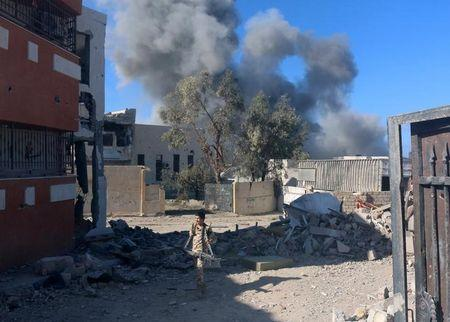 Fighter of Libyan forces allied with the U.N.-backed government walks as smokes rises following an air strike on Islamic State positions in Ghiza Bahriya district in Sirte