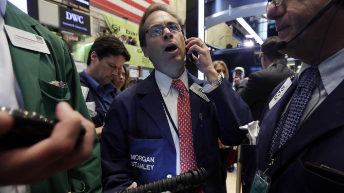 Trader Dudley Devine, center, works on the floor of the New York Stock Exchange, Friday, July 18, 2014. U.S. stocks are opening higher after Google, Honeywell and other big companies report their quarterly results. (AP Photo/Richard Drew)