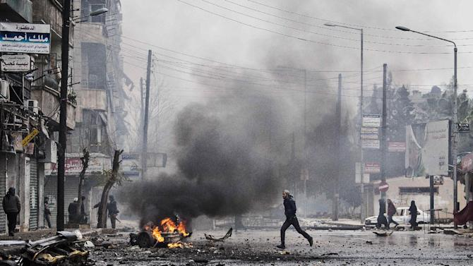 FILE - In this Dec. 17, 2012 file photo, a man runs between debris after a mortar shell hit a street killing several people in the Bustan Al-Qasr district of Aleppo, Syria. 2012 was a year of storms, of raging winds and rising waters, but also broader turbulence that strained our moorings. Old enmities and grievances resurfaced in the Middle East, clouding the legacy of the 2011 Arab spring. And the number of dead in the Syrian civil war passed 40,000. (AP Photo/Narciso Contreras, File)