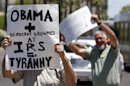 Several dozen tea party activists and other concerned citizens, wave signs and small American flags as they march outside the main Internal Revenue Service office on Tuesday, May 21, 2013, in Phoenix. The rally was one of many around the country after IRS officials acknowledged that some conservative groups received inappropriate attention and questioning. (AP Photo/Ross D. Franklin)