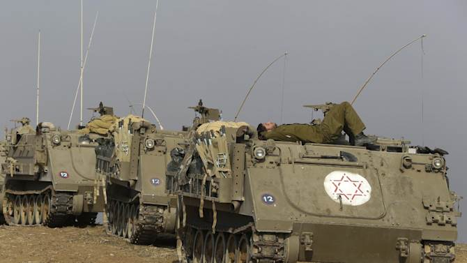 An Israeli soldier sleeps atop an armored medical vehicle as they form a convoy to be driven out of southern Israel, near the Israel Gaza Strip Border, Thursday, Nov. 22, 2012. A cease-fire agreement between Israel and the Gaza Strip's Hamas rulers took effect Wednesday night, bringing an end to eight days of the fiercest fighting in years and possibly signaling a new era of relations between the bitter enemies. (AP Photo/Lefteris Pitarakis)