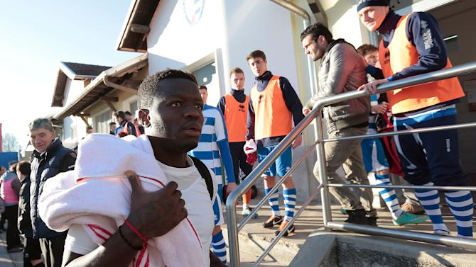 In this picture made available Friday, Jan. 4, 2013, AC Milan Ghana midfielder Sulley Muntari leaves the changing rooms as he walks past Pro Patria players in Busto Arsizio, near Milan, Italy, Thursday, Jan. 3, 2013. A friendly match between AC Milan and lower division club Pro Patria was abandoned Thursday after racist chants directed at Milan's black players, the latest incident of racial abuse that continues to blight the sport. After repeated chants directed his way, Ghana midfielder Kevin-Prince Boateng picked up the ball and kicked it at a section of the crowd in the 26th minute of the first half. Boateng then took off his shirt and walked off the pitch with his Milan teammates. Urby Emanuelson, Sulley Muntari and M'Baye Niang were also targeted by the chants. (AP Photo/Emilio Andreoli)