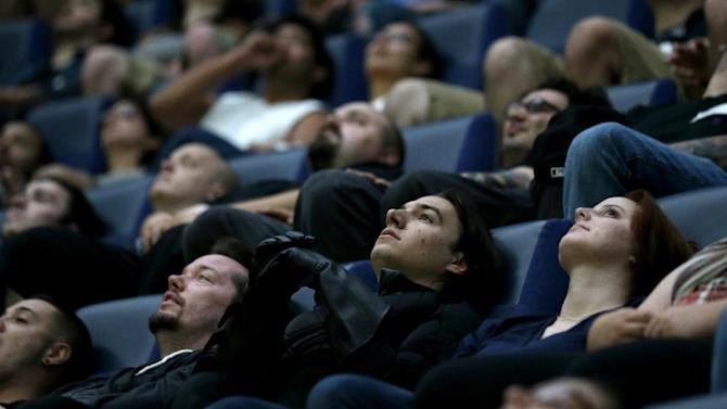 "FILE - This July 20, 2012 file photo shows a wide awake crowd watching the premier of ""The Dark Knight Rises"" inside the Liberty Science Center IMAX theater in Jersey City, N.J. Movie napping is a precarious affair and almost certainly as old as cinema itself. It strikes the overtired and the well-rested, film nuts and occasional theatergoers. Any which way, cinematic snoozing seems near epidemic proportions this awards season with buzz plus ZZZs for ""Lincoln,"" the 157-minute sung ""Les Miserables,"" the 169-minute ""The Hobbit: An Unexpected Journey"" and others cited as good for a snore.  (AP Photo/Julio Cortez, file)"