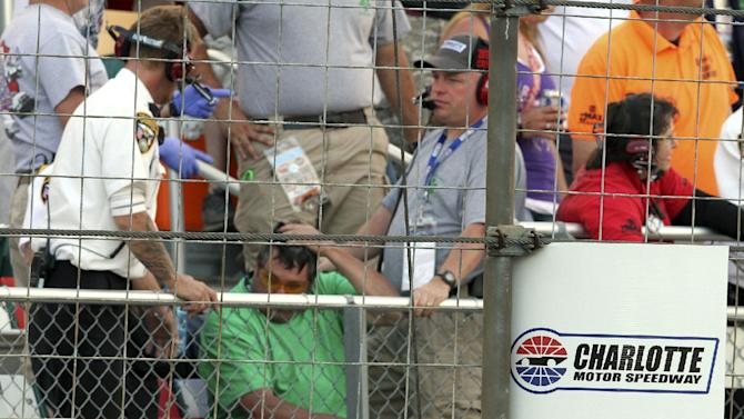 In this photo provided by Fernando Echeverria, security personnel assist a fan injured by a broken television camera cable during the NASCAR Sprint Cup series Coca-Cola 600 auto race at Charlotte Motor Speedway in Concord, N.C., Sunday, May 26, 2013. (AP Photo/Fernando Echeverria)