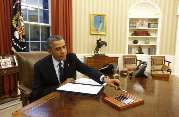 U.S. President Barack Obama reaches for a pen as he signs a bill in the Oval Office of the White House in Washington, November 27, 2013. According to the White House, Obama signed three bills into law, S. 252, H.R. 1848, and H.R. 3204. REUTERS/Larry Downing (UNITED STATES - Tags: POLITICS)