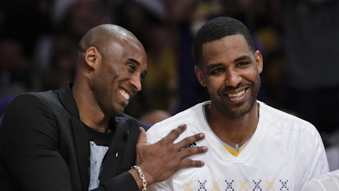 Los Angeles Lakers guard Kobe Bryant, left, sits on the bench with forward Shawne Williams during the first half of the Lakers' NBA basketball game against the Miami Heat in Los Angeles, Wednesday, Dec. 25, 2013. (AP Photo/Chris Carlson)